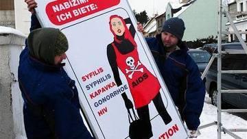 Рабочие готовятся повесить плакат в чешском городе Хомутов