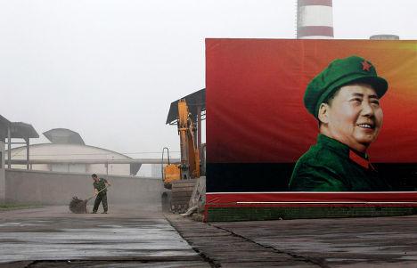 Рабочий убирает возле плаката Мао Цзэдуна на тепловой электростанции Nanjie Cun Group