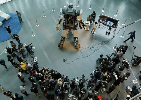 Представители СМИ у боевого робота «Kuratas» на выставке в Токио, Япония
