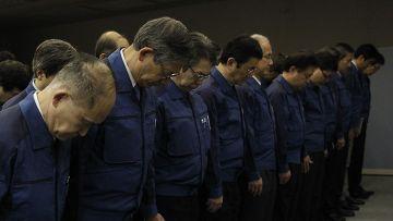 Сотрудники Tokyo Electric Power Co (TEPCO) во время минуты молчания в память жертв землетрясения и цунами 2011 г.