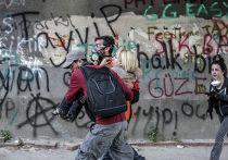 Протестующие несут пострадавшую в результате столкновения с полицией девушку в Стамбуле