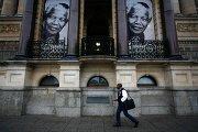 Мужчина проходит мимо баннеров с портретами Нельсона Манделы в Кейптауне