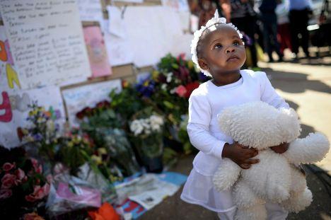 Девочка стоит возле плакатов в поддержку Нельсона Манделы в Претории