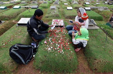 Жители Индонезии посещают кладбище накануне священного месяца Рамадан