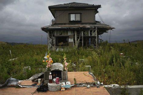 Памятник жертвам перед заброшенным домом в эвакуированном городе Нами, префектура Фукусима