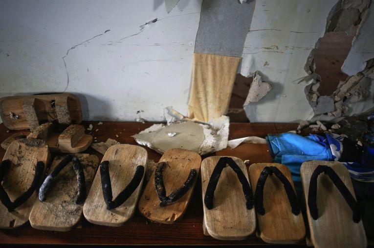 Обувь, оставленная в общественном центре, в разрушенной цунами части города Нами, префектура Фукусима