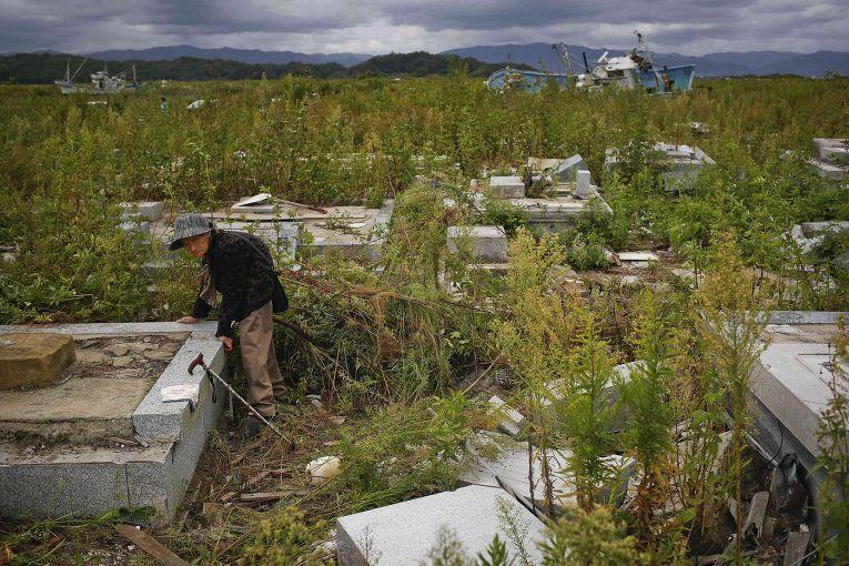Старая женщина на кладбище в разрушенной цунами части города Нами, префектура Фукусима