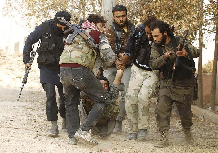 Солдаты Свободной сирийской армии несут тело товарища, раненого в столкновениях с правительственными войсками