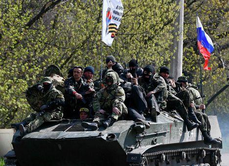 Люди, одетые в военную форму на боевой технике с флагом России в Славянске