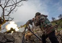 Военнослужащий правительственной армии Сирии ведет огонь из пулемета на позиции войск на одной из вершин возле города Кесаб, захваченного исламистами.