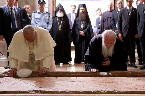Папа Римский Франциск и Патриарх Константинопольский Варфоломей I прикасаются к камню помазания в Иерусалиме