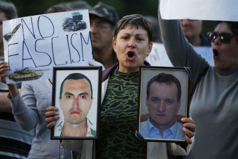 Женщина с портретами людей, погибших в столкновениях на востоке Украины, на пророссийском митинге в Донецке