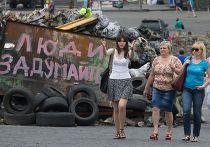 Люди идут вдоль баррикад на площади Независимости в Киеве