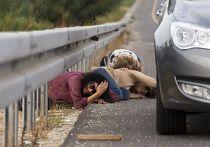 Израильтяне укрываются за машинами на дороге после того, как прозвучала сирена воздушной тревоги