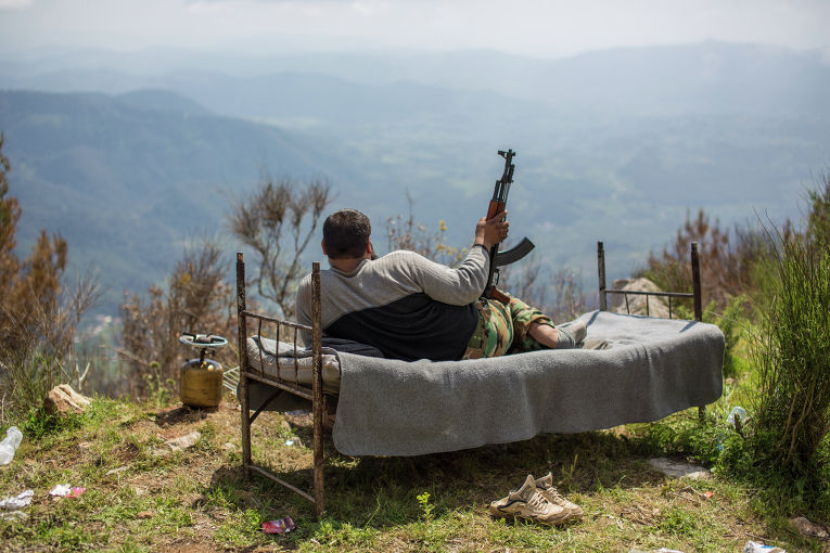 Сирийский солдат лежит на кровати на господствующей высоте у города Кесаб