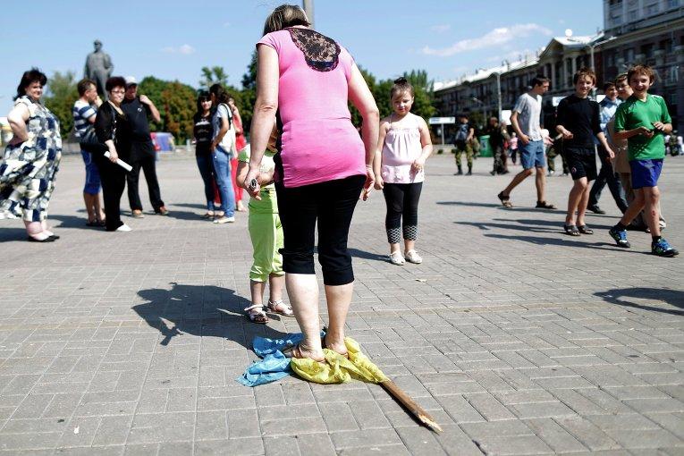 Женщина топчет украинский флаг на площади Ленина в Донецке