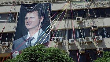 Плакат с портретом президента Сирии Башаром Асадом на здании в Дамаске