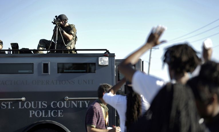 Полицейский целится в толпу во время акции протеста в Фергюсоне