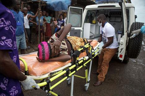 Беременная женщина с подозрением на лихорадку Эбола на носилках скорой помощи в городе Фритаун, Сьерра-Леоне 19 сентября 2014