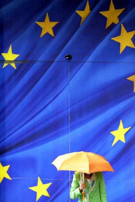 Прохожий с зонтом у символики ЕС в Брюсселе