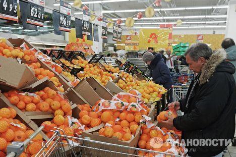Посетитель выбирает фрукты в одном из магазинов торговой сети «Ашан» в Москве