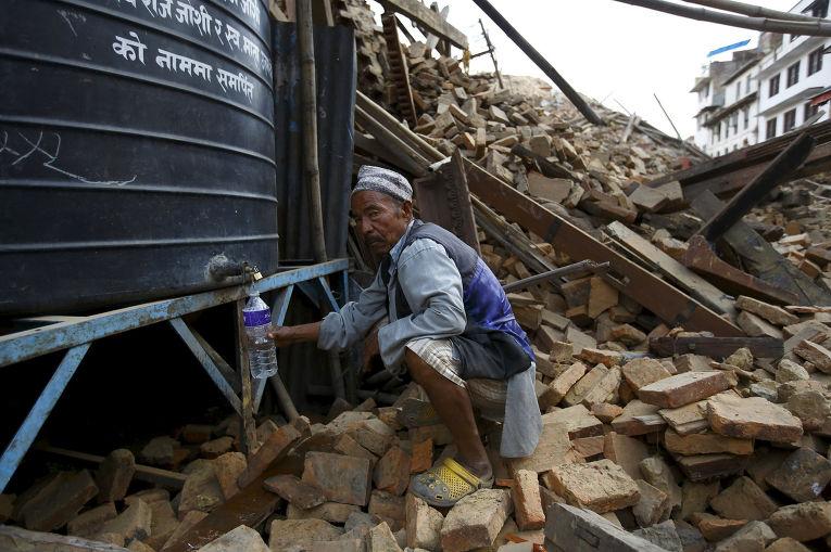 Мужчина набирает воду рядом с разрушенным храмом в Катманду
