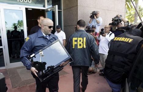 Сотрудники ФБР выносят документы и компьютеры из офиса конфедерации футбола Северной и Центральной Америки и стран Карибского бассейна
