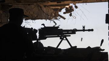Ополченец стреляет по позициям украинских военных из руин Донецкого аэропорта, июнь 2015 года