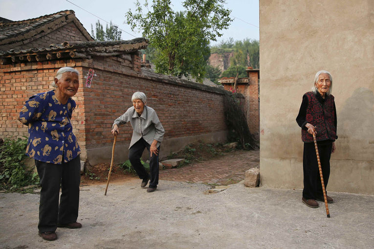 Цзюйсян Хао (справа) во дворе своего дома в городе Гучэн, провинция Шаньси