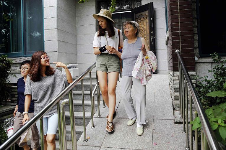 Волонтеры помогают Кир Вон Окх по пути на еженедельный митинг у скульптуры «женщины для утешения»