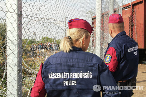 Венгерские полицейские наблюдают за беженцами на сербской стороне
