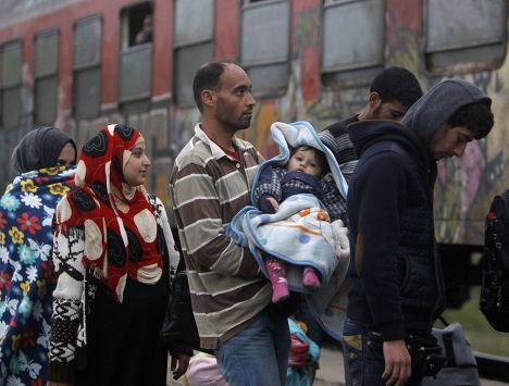 Беженцы садятся на поезд, идущий в Сербию, на станции в городе Гевгелия, Македония