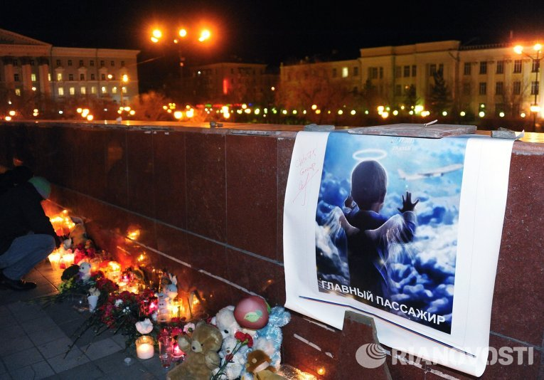 Свечи, игрушки и цветы на площади Ленина в Чите во время акции памяти жертв крушения самолета А-321