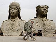 Американские солдаты проходят мимо бронзовых бюстов Саддама Хусейна в Зеленой зоне Багдада