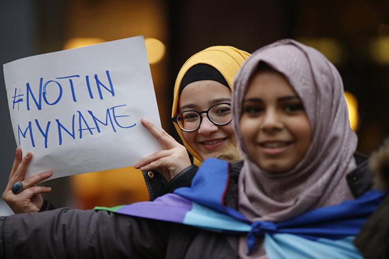 Девушки-мусульманки с табличкой «Не от моего имени» во время акции протеста против терроризма в Милане