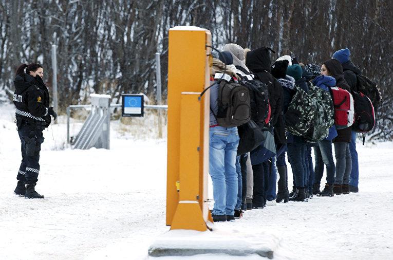 Норвежский офицер полиции инструктирует мигрантов после пересечения российско-норвежской границы
