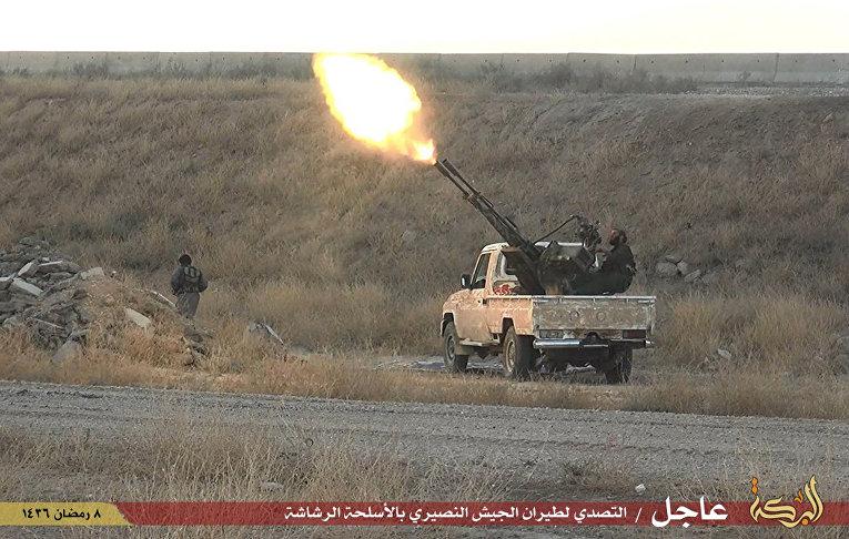 Боевики «Исламского государства» стреляют из зенитного орудия в городе Хассакех на северо-востоке Сирии