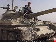 Боец ИГИЛ на танке, захваченном у сирийских военных, в городе Эль-Карьятейн