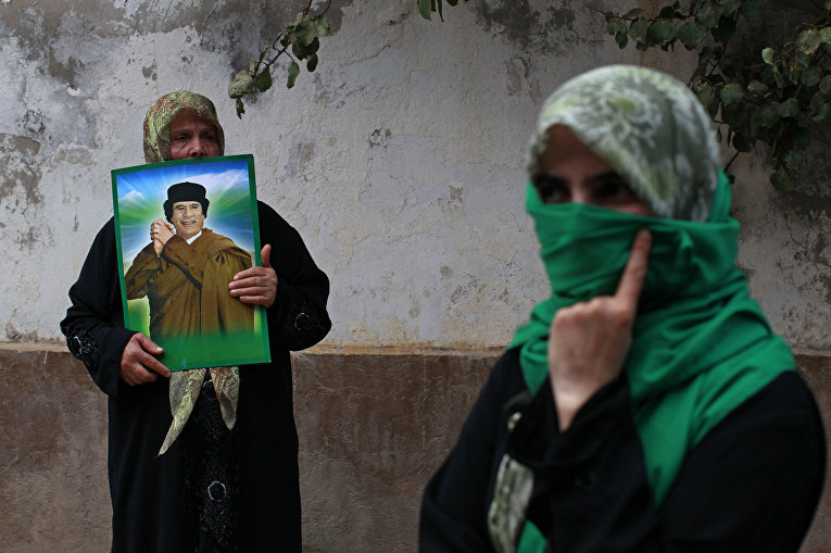 Женщины с портретом Муаммара Каддафи на акции протеста против авиударов НАТО у здания посольства Венгрии в Триполи, апрель 2011 года
