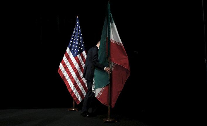 Сотрудник убирает флаги после совместного фотографирования лидеров государств-участников соглашения по иранской ядерной программе