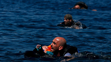 Беженец с ребенком плывет к острову Лесбос после кораблекрушения
