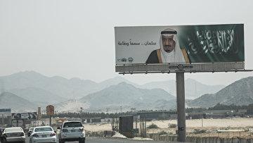 Щит с портретом короля Салмана и словами «Салман, мы слушаем и повинуемся» у шоссе поблизости от Мекки