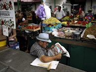 Продавец на рынке в Белграде читает газету в ожидании покупателей