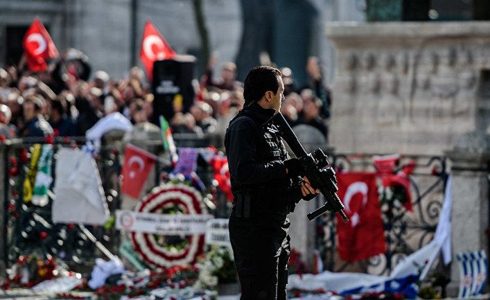 Полицейский рядом с памятником жертвам теракта на площади Султанахмет в Стамбуле