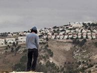 Израильтянин смотрит на город Маале-Адумим на Западном берегу реки Иордан