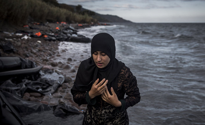 Женщина, прибывшая на греческий остров Лесбос на резиновой лодке из Турции