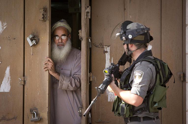 Палестинец закрывает магазин во время столкновений палестинских протестующий с израильской армией