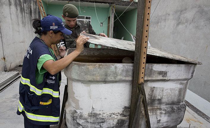 Медицинский работник и солдат проверяют контейнер в рамках операции по уничтожению комаров вида Аedes Аegypti, переносящих вирус Зика