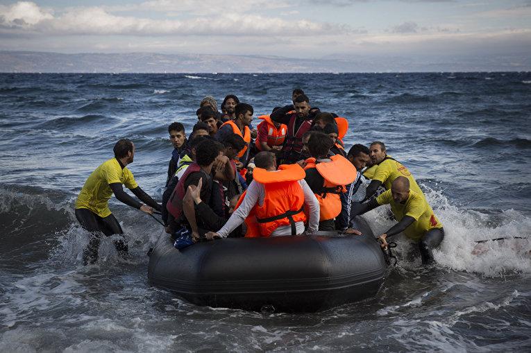 Спасатели помогают беженцам причалить у берега греческого острова Лесбос