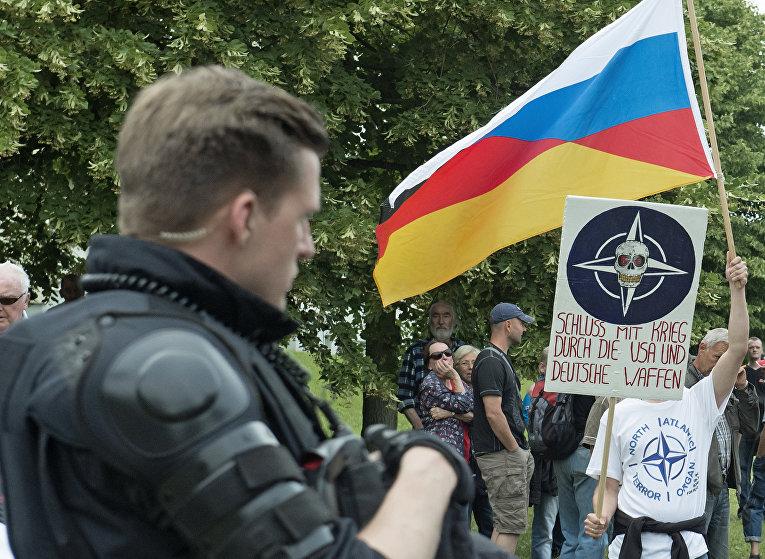 Митингующий держит в руках выдуманный Русско-Германский флаг на митинге против мигрантов